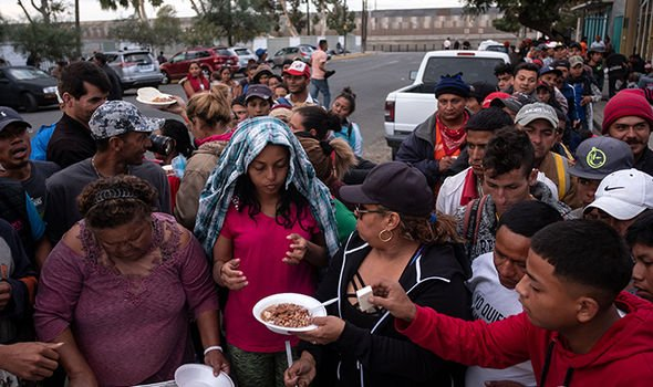 Central American migrants line up for food outside a temporary shelter