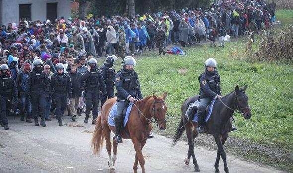 Los migrantes son escoltados por la policía a caballo