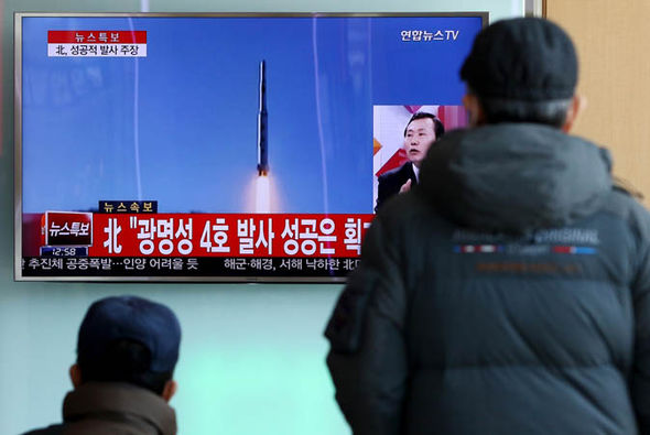 Koreans watch a missile test from the North