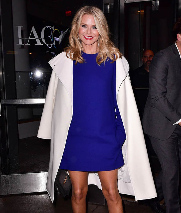 Christie Brinkley smiling in blue dress