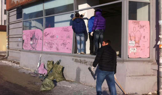 People look at damage to a shop following sightings of a falling object in the sky in the Urals city of Chelyabinsk