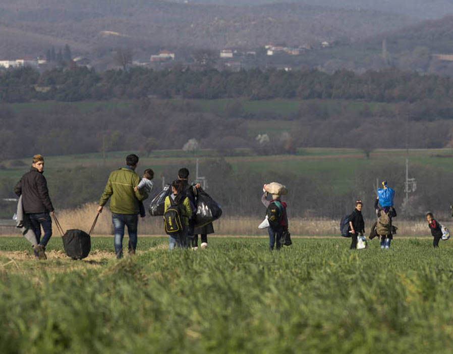 Refugee families walk through fields under mountains towards the Greek-Macedonia border on March 03, 2016 in Idomeni, Greece