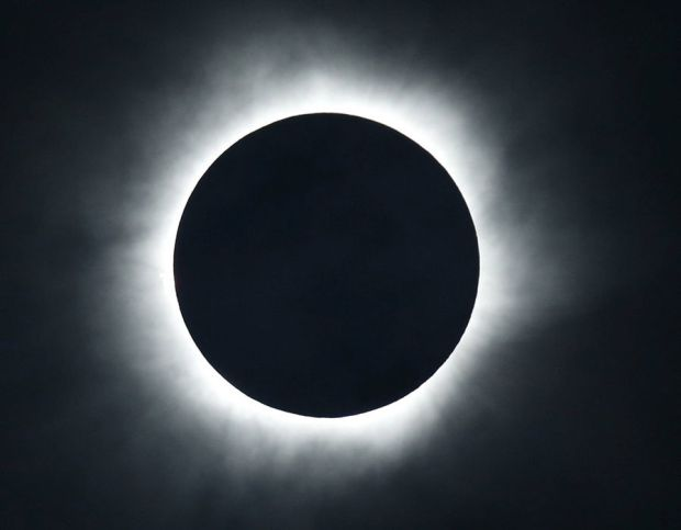 A solar eclipse is seen from the beach of Ternate island, Indonesia