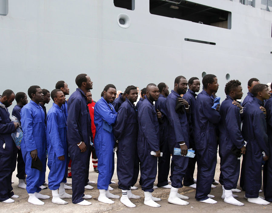 Migrants are lined up as they disembark the German naval vessel Frankfurt Am Main in the Sicilian harbour of Pozzallo