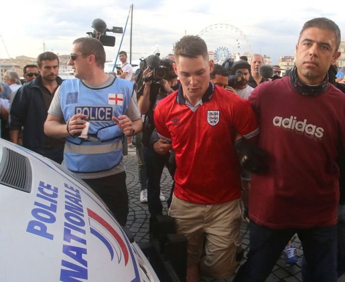 English police officers (blue tops left) watch as a French police officer restrains a football fan wearing an England top (centre)