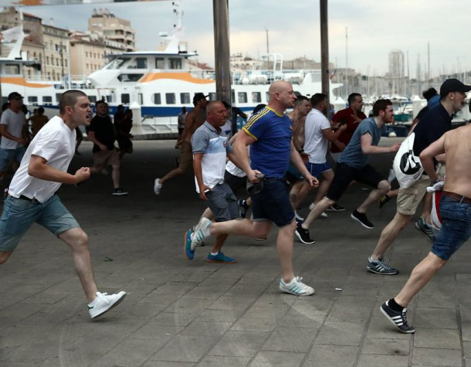 England football fans run toward other football fans as England fans clash with police and local football supporters
