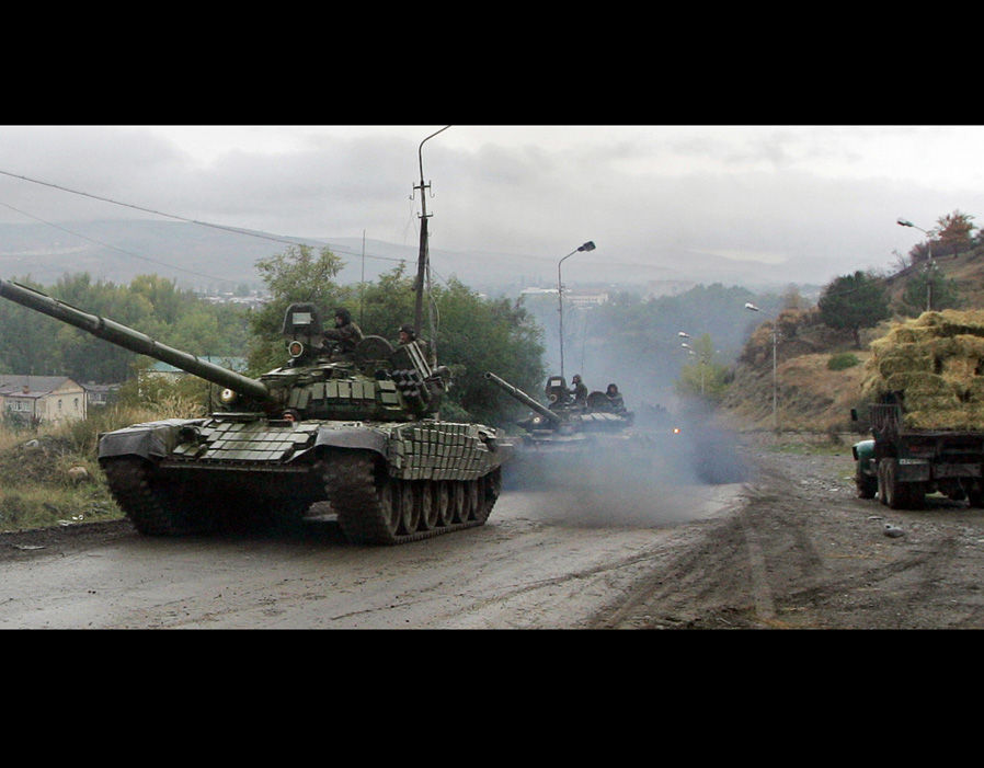 Russian tanks drive along a road outside the town of Karaleti, a village near the Russian-controlled buffer zone