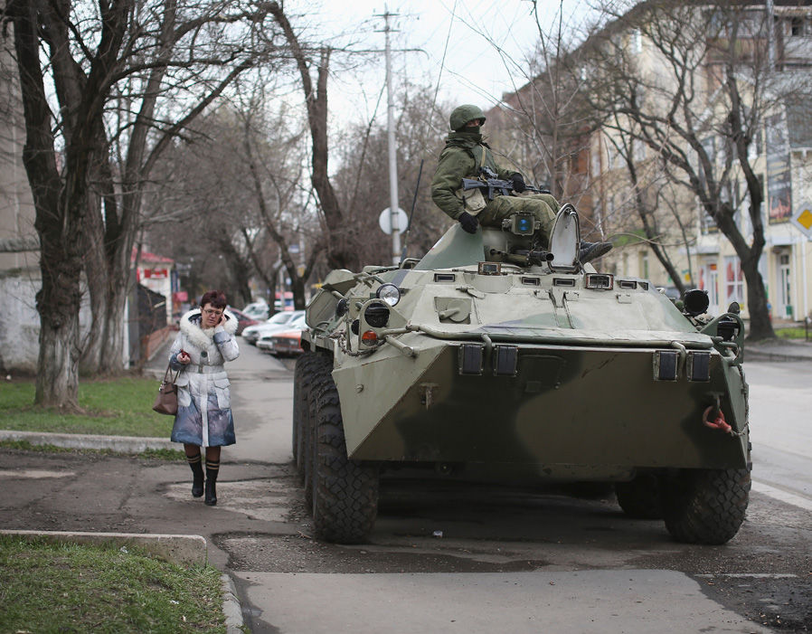A woman walks past a Russian military personnel carrier outside a Ukrainian military base