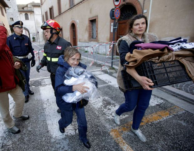 Two women carry their belongings after an earthquake in Visso