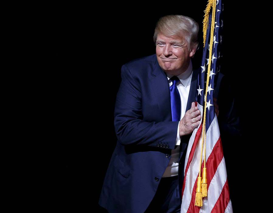 U.S. Republican presidential candidate Donald Trump hugs a U.S. flag as he takes the stage for a campaign town hall meeting in Derry