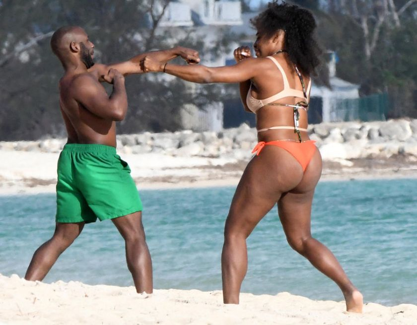 Serena Williams has a playful boxing match with her male friend on holiday
