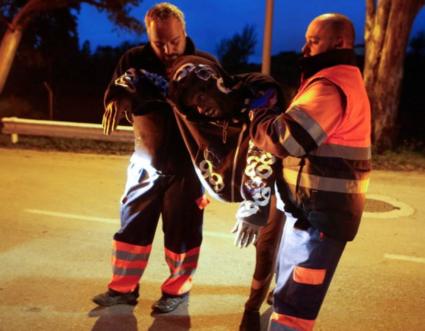 An African migrant is helped by emergency personnel after crossing the border fence between Morocco and Spain's north African enclave of Ceuta