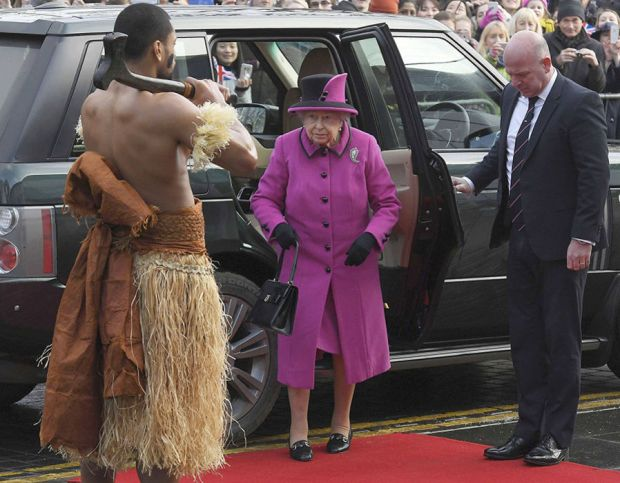 Britain's Queen Elizabeth looks towards a man dressed in traditional costume as she arrives to view an exhibition on Fiji at the Sainsbury Centre for Visual Arts, University of East Anglia in Norwich, eastern England