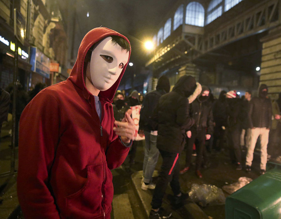 A man wearing a Guy Fawkes mask attends a protest against police brutality after a young black man, 22-year-old youth worker named Theo, was severly injured during his arrest earlier this month in Bobigny, as people gather at a demonstration in Paris