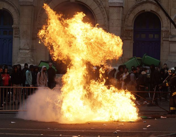 French firemen try to extinguish burning dustbins as students gather during a demonstration against police brutality, following the alleged rape of Theo, outside the
