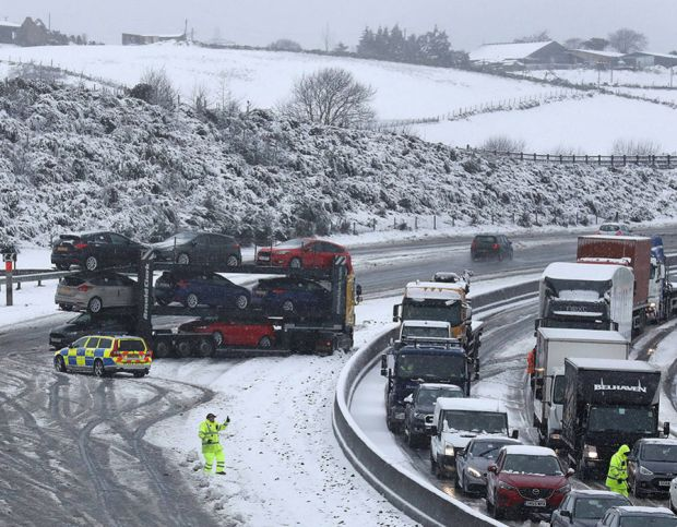 A jack-knifed car transporter near Banknock on the M80 near Falkirk during early morning snowfall, as flights have been cancelled and commuters were warned they faced delays after Storm Doris reached nearly 90mph on its way to batter Britain