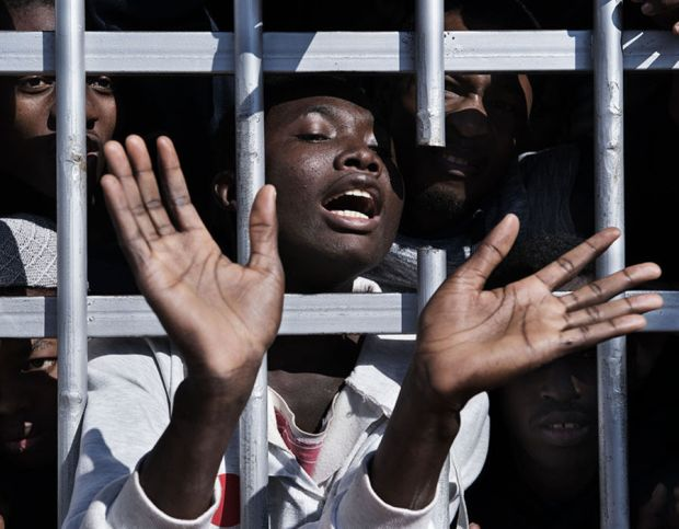 A migrant gestures from behind the bars of a cell at a detention centre in Libya