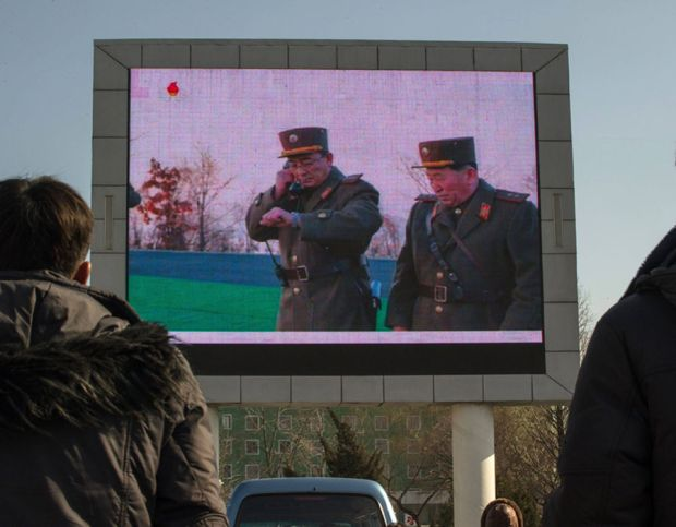 People watch news footage of a missile launch on a giant television screen outside the main railway station in Pyongyang on March 7, 2017