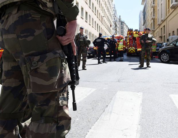 French soldiers, policemen and firefighter vehicles are seen at the site of a police search are seen at the site of a police search on April 18, 2017 in the third district of Marseille, following the arrest of two men suspected of preparing an attack