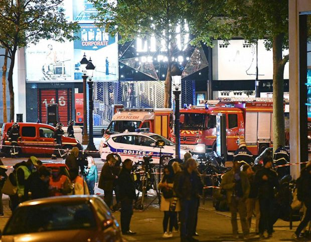 People stands in a street near the site of a shooting at the Champs Elysees in Paris