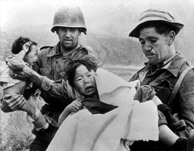 Soldiers take care for two lost infants who were found alongside the road to Pyongyang