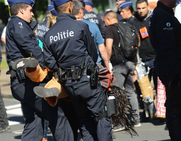Police detain a demonstrator during a protest against a NATO summit in Brussels