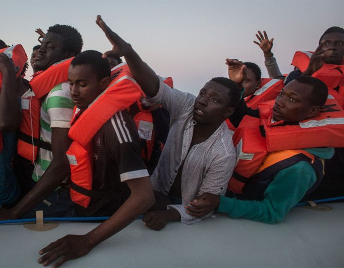 Refugees and migrants wait in a small rubber boat to be rescued off Lampedusa, Italy