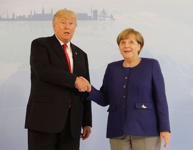 German Chancellor Angela Merkel (R) and US President Donald Trump  shake hands prior to a bilateral meeting on the eve of the G20 summit in Hamburg