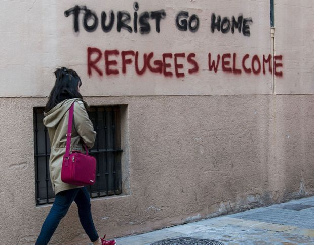 woman walks next to a grafitti that  reads 'Tourist go home, Refugees welcome' in downtown Palma, Majorca