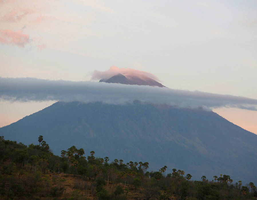 A view of Mount Agung, a volcano on the highest alert level, as the sun rises from Amed on the resort island of Bali