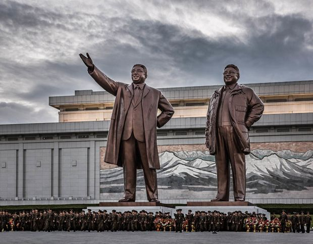 Mansudae Grand Monument. An enormous bronze statue of President Kim Il Sung and Leader Kim Jong Il, downtown Pyongyang. Image taken the day before Liberation Day where military personnel are visiting the monument to lay flowers for the leaders.  Liberatio