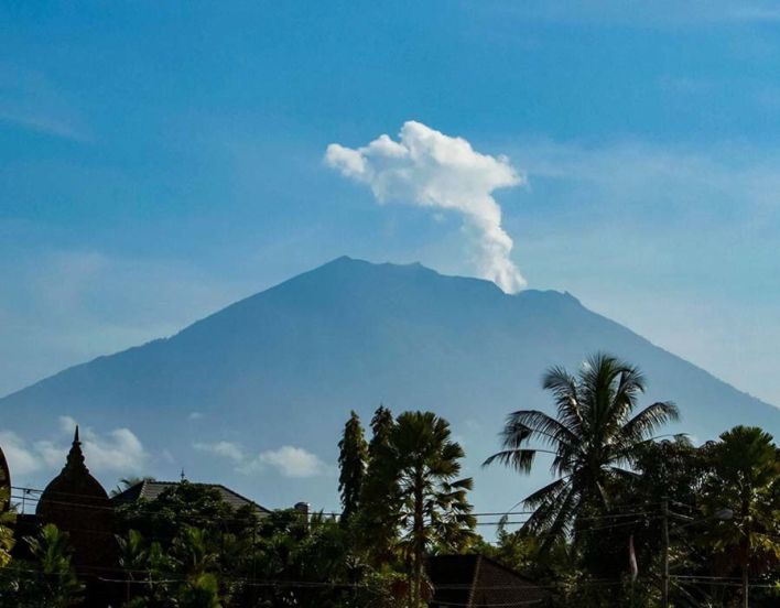 Mount Agung volcano spews steam and smoke into the air as seen from Bangli on Indonesia's resort island of Bali on October 23, 2017
