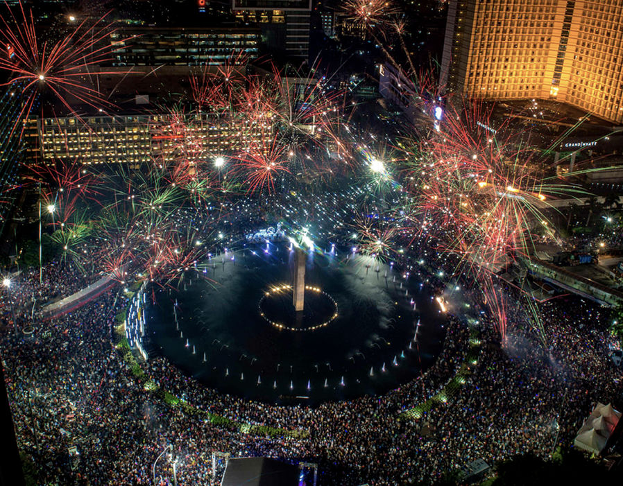 Fireworks explode over the Selamat Datang Monument in downtown Jakarta as Indonesia welcomes the new year