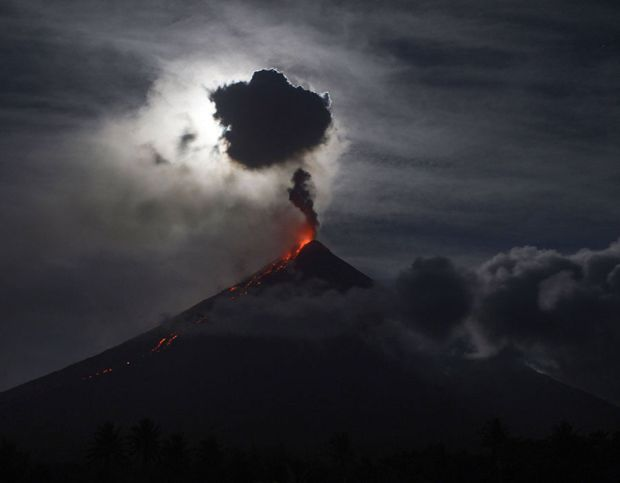 The 'super blue blood moon' obscured by clouds illuminates Mayon volcano