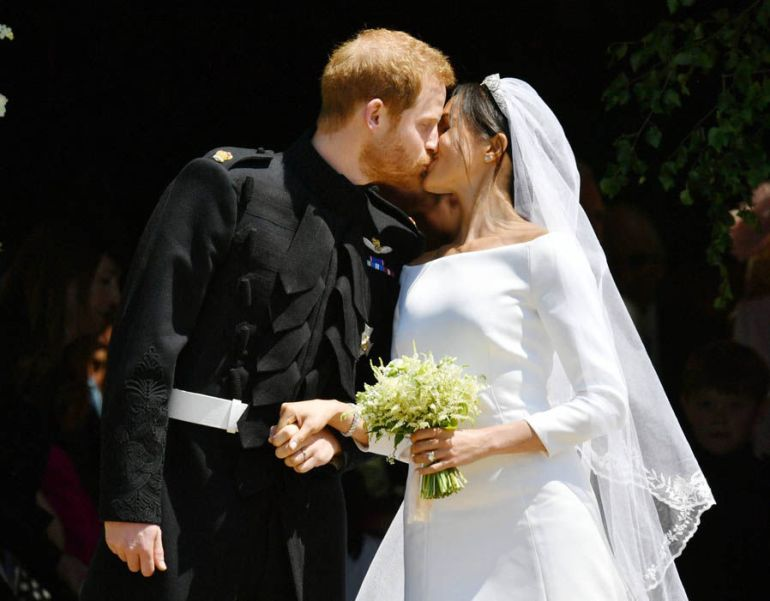 Prince Harry and Meghan Markle kiss on the steps of the chapel of St. George
