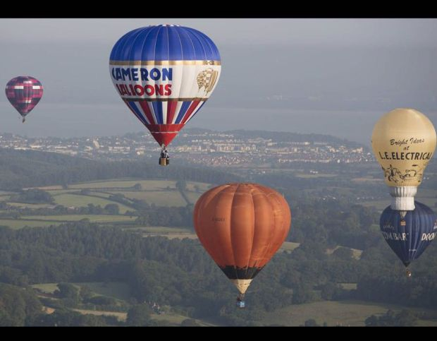 Hot air balloons lift off during a mass ascent at the 36th International Balloon Fiesta at Ashton Court
