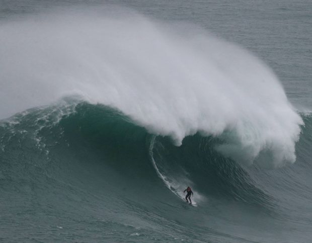A surfer rides a big wave during a tow-in surfing session at the Praia do Norte