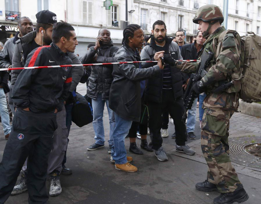 French soldier checks the identity papers of a man during an operation to catch Paris attack fugitives in Saint-Denis