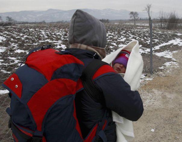 Un refugiado lleva un bebé envuelto en una manta mientras caminaba en temperaturas bajo cero hacia la frontera con Serbia desde el centro de tránsito para los refugiados cerca de la aldea del norte de Macedonia de Tabanovce