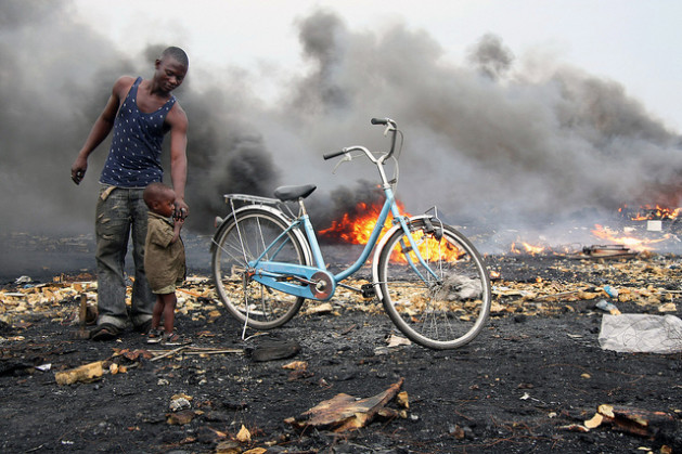 The Agbogbloshie e-Wasteland in Ghana. Fires are set to wires and other electronics to release valuable copper and other materials. The fires blacken the landscape, releasing toxic fumes. Credit: Blacksmith Institute