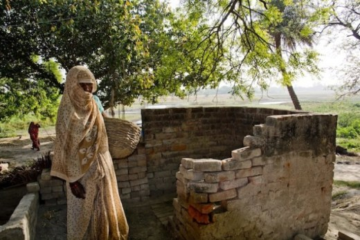A Dalit woman stands outside a dry toilet located in an upper caste villager's home in Mainpuri, in the northern Indian state of Uttar Pradesh. The village has witnessed major violence against those who have tried to leave the profession of 'manual scavenging'. Credit: Shai Venkatraman/IPS