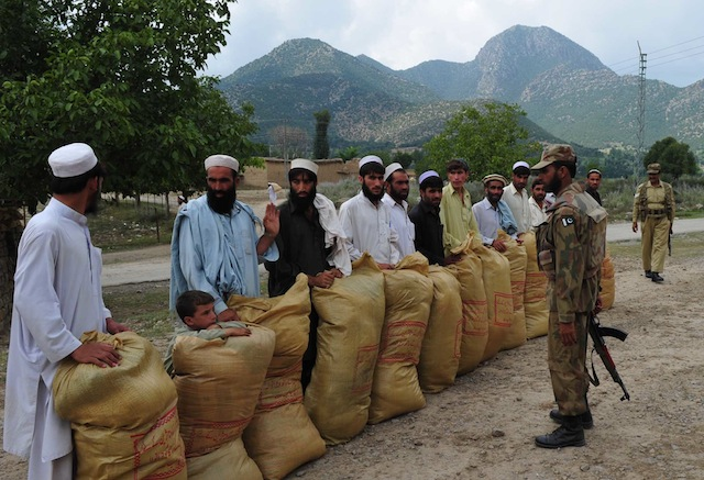 Army officers stand opposite displaced families as they collect their monthly allocation of food supplies in northern Pakistan. Credit: Ashfaq Yusufzai/IPS