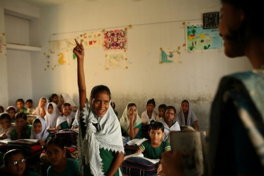 A student at the Hazi Ibrahim Government Primary School in Bangladesh's capital, Dhaka, raises her hand in response to her teacher's questions. Credit: Shafiqul Alam Kiron/IPS
