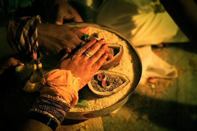A couple performs a ritual at an Indian wedding. Experts say that every year, thousands of women experience marital rape, which is yet to be decriminalised in India. Credit: Naveen Kadam/CC-BY-2.0