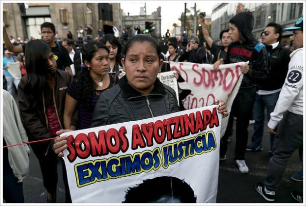 A protester at a rally against the disappearance of 43 students in the southwestern Mexican state of Guerrero holds a sign that reads: 'We Are Ayotzinapa. We Demand Justice.' Credit: Montecruz Foto/CC-BY-SA-2.0
