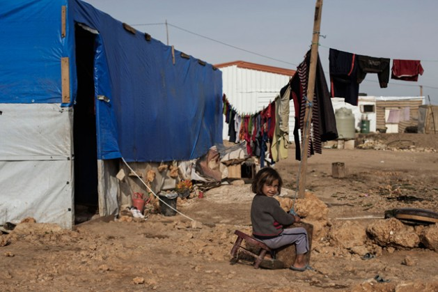 A young Syrian girl sits on a broken chair by her tent in Faida 3 camp, an informal tented settlement for Syria refugees in Bekaa Valley, Lebanon.  Credit: UNICEF/Alessio Romenzi