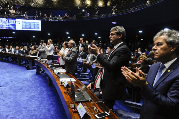 A group of weary senators applaud at the end of the marathon session that decided to immediately suspend President Dilma Rousseff during an impeachment trial for her removal. Credit: Marcos Oliveira/Agência Senado