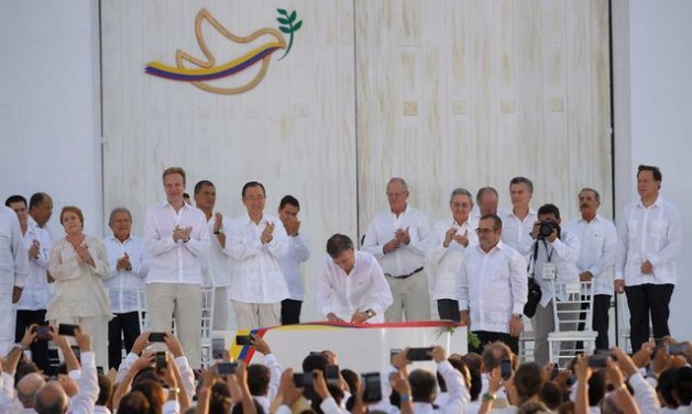 Colombian President Juan Manuel Santos signs the peace agreement, observed by FARC chief Rodrigo Londoño, Latin American presidents and other dignitaries, in an open-air ceremony in the city of Cartagena de Indias. Credit: Colombian presidency