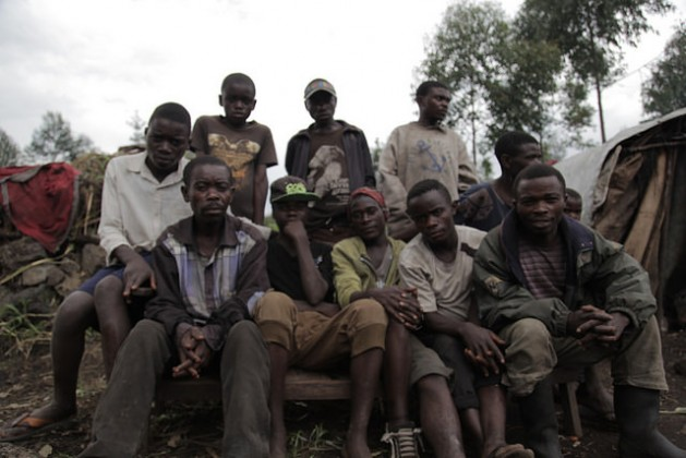 A group of young Mbuti men from Biganiro, DRC, sit in front of their houses, which consist of makeshift structures made of wood and plastic sheeting. Credit: Zahra Moloo/IPS