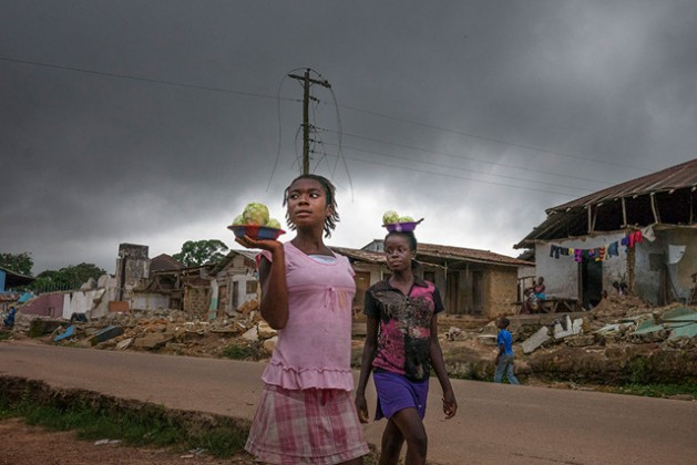 Infrastructure across Liberia, including electricity installations, was destroyed during the country's protracted civil war (1989-2003). Above, girls in the town of Totota in Bong County walk past homes that are being demolished as the government rebuilds roadways. Photo: UN Women